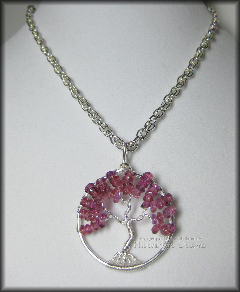 Stunning, semi-precious Rhodolite Garnet rondelles in a bright raspberry pink color are set in sterling silver wire to form a beautiful Tree of Life pendant.