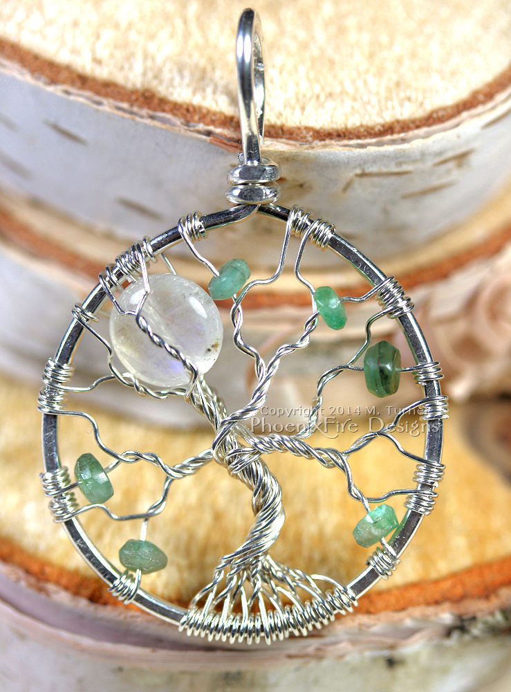 Custom rainbow moonstone full moon tree of life with scattering of emeralds.