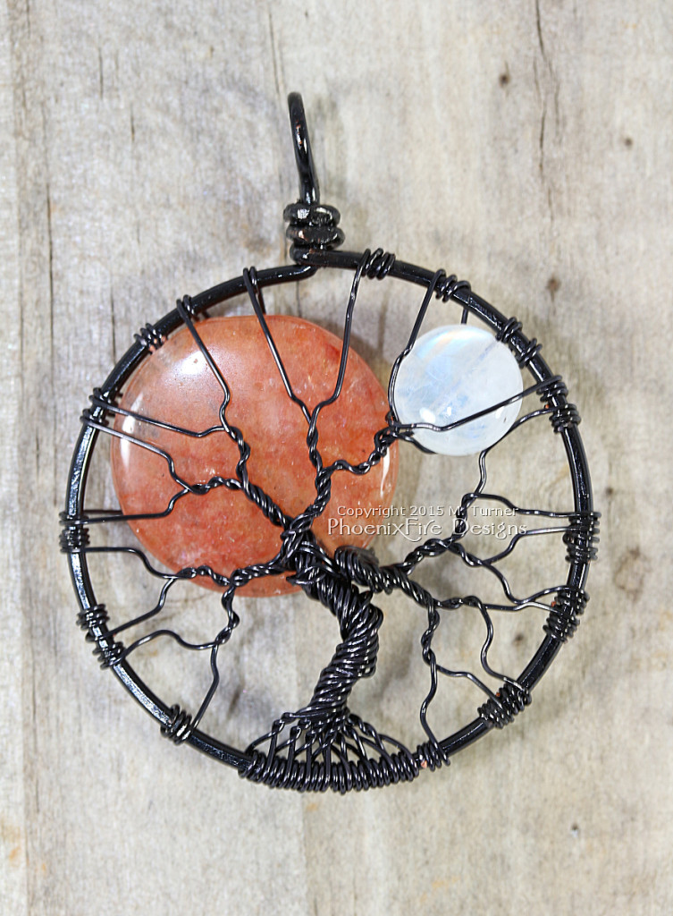 Large, orange opal sun and small rainbow moonstone moon rest together in this black wire wrapped tree of life pendant by PhoenixFire Designs.