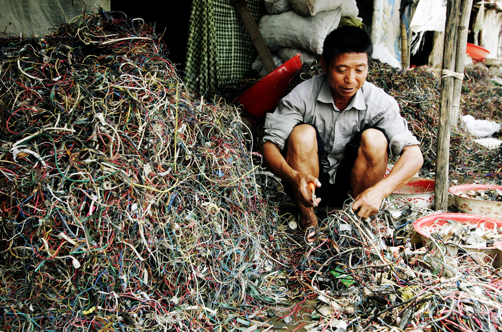 epa000471501 A worker rummages through electronic waste for the purpose of salvaging metals and other materials for resale in Guiyu, south China's Guangdong province, Friday 01 July 2005.  Electronic waste, illegally imported here from developed countries, is causing severe environmental damage and exposing workers to highly toxic chemicals and heavy metals.  EPA/MICHAEL REYNOLDS