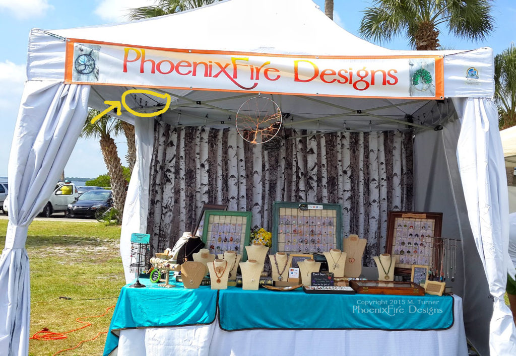 PhoenixFire Designs vendor booth displaying Undercover R-3 CRS curtain hanging system usage.